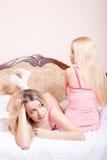 2 attraktive nette junge blonde Frauen der Freundinnen recht in rosa Pyjamas einer von ihnen ist Lügenentspannung im Bett Stockbild