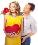 Attraktive Paare der Liebhaber. Mann stellt Blume dar. lizenzfreie stockfotos