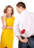 Attraktive Paare der Liebhaber. Mann stellt Blume dar. lizenzfreie stockfotografie