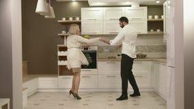 Attraktive Paare, die den Spaß zusammen tanzt in der Küche haben stock video