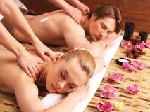 Attraktive Paare, die in einem Badekurortsalon liegen Lizenzfreie Stockbilder