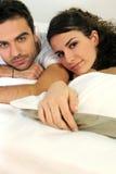 Attraktive Paare, die im Bett liegen Stockfotografie