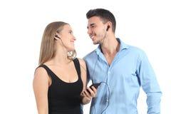 Attraktive Paare, die Musik mit Kopfhörer teilen stockfotografie
