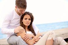 Attraktive Paare, die zusammen auf einem Pier sitzen Stockfotos