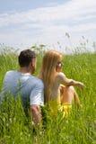 Attraktive Paare, die Zusammengehörigkeit auf Wiese genießen lizenzfreie stockfotografie