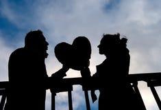 Attraktive Paare im Schattenbild, das ein Liebesherz hält Lizenzfreies Stockbild