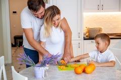 Attraktive Paare mit der schwangeren Frau, die in der Küche zusammen mit Kind frühstückt stockfotografie