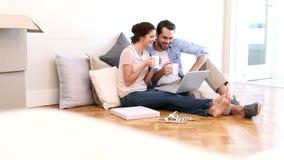 Attraktive Paare unter Verwendung des Laptops auf dem Boden stock footage