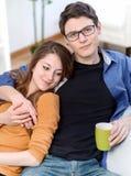 Attraktive Paare von den Liebhabern, die auf einem Sofa nimmt ein heißes Getränk sitzen Lizenzfreie Stockfotografie