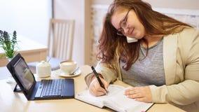 Attraktive PlusgrößenGeschäftsfrau, die in der hellen Kaffeestube arbeitet stockfotos