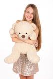 Attraktive positive Blondine, die einen Teddybären umarmt Stockfotografie