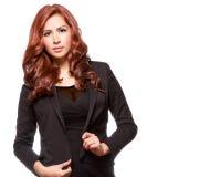 Attraktive redheaded Geschäftsfrau in der schwarzen Ausstattung Stockfotos