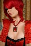 Attraktive Redheadfrau im roten Korsett stockbild