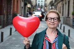 Attraktive reife Dame, die ein riesiges Herz hält lizenzfreie stockfotos