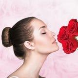 Attraktive riechende Rosen der jungen Frau Lizenzfreie Stockfotos