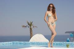 Attraktive Rothaarigefrau im Pool mit einem Cocktail Lizenzfreie Stockbilder