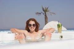 Attraktive Rothaarigefrau im Pool mit einem Cocktail Lizenzfreies Stockfoto