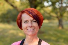 Attraktive Rothaarigefrau mit einem freundlichen Lächeln Stockfotografie