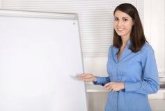 Attraktive schöne Geschäftsfrau vor einer Flip-Chart lizenzfreie stockfotos