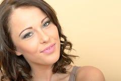 Attraktive schöne junge Frau, die in Richtung zur Kamera lächelt lizenzfreie stockfotografie