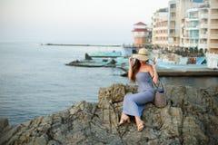 Attraktive Schönheit mit dem weißen Strohhut, der weg Meer und Sonnenuntergang oder Sonnenaufgang betrachtet Frau mit Sommerstran Lizenzfreie Stockfotos