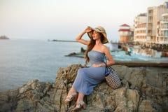 Attraktive Schönheit mit dem weißen Strohhut, der weg Meer und Sonnenuntergang oder Sonnenaufgang betrachtet Frau mit Sommerstran Stockfoto