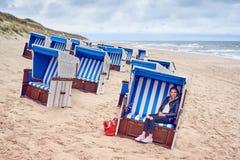 Attraktive schlanke blonde Frau, die in einer Strandhütte sitzt Stockfotos