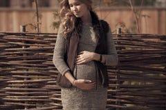 Attraktive schwangere Frau in der gemütlichen Kleidung an der Landschaft lizenzfreies stockfoto