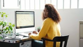 Attraktive schwarze Frau arbeitet an Computer im Büro stock video footage