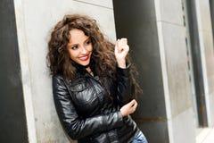 Attraktive schwarze Frau in städtischer Hintergrund tragendem ledernem jacke Lizenzfreie Stockfotografie