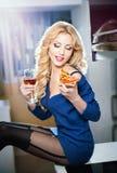 Attraktive sexy blonde Frau mit heller blauer Bluse und schwarzen den Strümpfen, die das Lächeln aufwerfen, eine Pizzascheibe esse Lizenzfreie Stockfotos