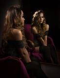 Attraktive Blondine mit den schwarzen langen Strümpfen, die das Sitzen vor einem Spiegel aufwerfen Portrait der sinnlichen j Lizenzfreie Stockbilder
