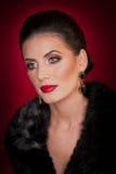 Attraktive sexy junge Frau, die einen Pelzmantel aufwirft im Studio auf dunklem purpurrotem Hintergrund trägt Porträt der sinnlic lizenzfreie stockfotografie