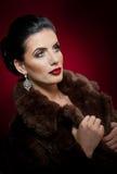 Attraktive sexy junge Frau, die einen Pelzmantel aufwirft im Studio auf dunklem purpurrotem Hintergrund trägt Porträt der sinnlic lizenzfreies stockbild