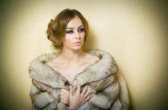 Attraktive sexy junge Frau, die einen Pelzmantel provozierend aufwirft Innen trägt Porträt der sinnlichen Frau mit kreativem Haar Lizenzfreies Stockfoto