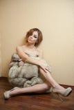 Attraktive sexy junge Frau eingewickelt in einem Pelzmantel, der auf dem Boden im Hotelzimmer sitzt Weibliches Sein der sinnliche Stockbilder