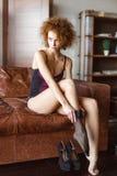 Attraktive sinnliche junge gelockte Frau im Korsett, das schwarze Strümpfe trägt stockfotos
