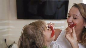 Attraktive Spaßfamilie hat Spaß mit Paprikapfeffer zu Hause in der Küche Die Mädchen mit dem langen Haar im weißen Kleid stock video footage