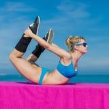 Attraktive Sportlerin in der blauen Sportkleidung und in der Sonnenbrille, die e tut Lizenzfreie Stockbilder