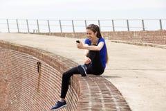 Attraktive sportliche Frau, die auf Wand mit Musik sitzt Stockfoto