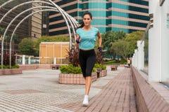 Attraktive sportliche junge Frau, die auf Pflasterung läuft lizenzfreie stockfotografie
