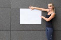 Attraktive sportliche junge Frau, die ein weißes Zeichen hält Lizenzfreie Stockfotografie