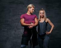 Attraktive sportliche Paare über grauem Hintergrund Lizenzfreie Stockfotos