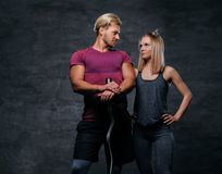 Attraktive sportliche Paare über grauem Hintergrund Stockbilder