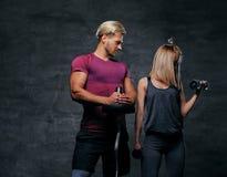 Attraktive sportliche Paare über grauem Hintergrund Stockfoto