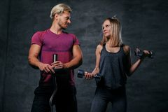 Attraktive sportliche Paare über grauem Hintergrund Lizenzfreie Stockbilder