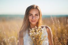 Attraktive Stellung der jungen Frau, die in der Wiese auf Sonnenuntergang lächelt stockbild
