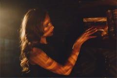 Attraktive Stellung der jungen Frau im Strahl des Lichtes und des Berührens eines Buches lizenzfreies stockfoto