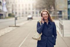 Attraktive stilvolle blonde Frau, die auf ihrem Smartphone plaudert Lizenzfreies Stockfoto