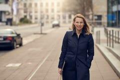 Attraktive stilvolle blonde Frau, die ihren Arbeitsplatz verlässt Stockfoto